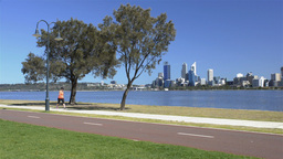 A woman exercising along the Swan River in Perth Stock Video Footage