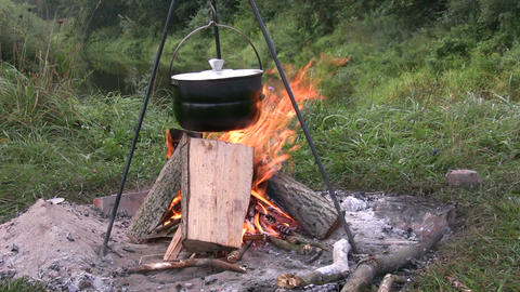 Preparing food in pot above bonfire 2 Footage
