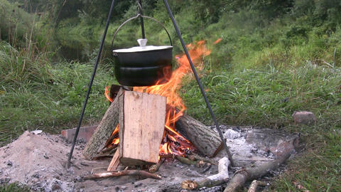 Preparing food in pot above bonfire 2 Stock Video Footage