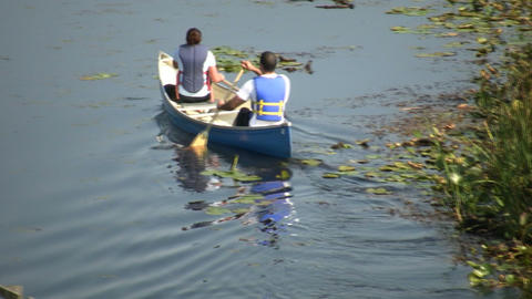 Couple is canoeing down river on sunny day (High Definition) Footage