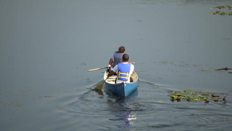 Couple is canoeing down river on sunny day (High Definition) Stock Video Footage