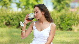 Woman Sitting On Grass Drinking Red Wine Footage