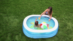 Mother And Daughter Having Fun In An Inflatable Pool Footage