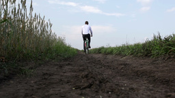 Guy Dressed In Formal Cycling In The Fields Footage