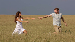 Young Couple Enjoying Freedom Running Across The Wheat Field Footage