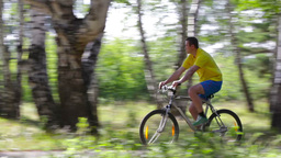 Male Cyclist Following The Path In The Summer Forest stock footage