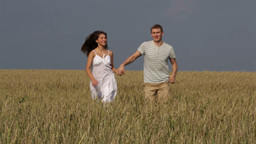 Happy Rural Couple Running Across The Field Holding Hands Footage
