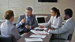Businesspeople Being Involved In A Heated Discussion With Their Mature Colleague Footage