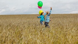 Little Friends Having Fun In The Rural Area Running With Colorful Balloons Footage