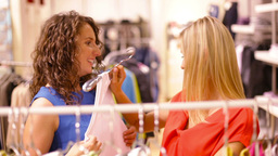 Young Women Choosing Clothes Hanging On The Racks Footage
