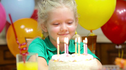 Cute Little Girl Thinking Over Her Birthday Wish And Blowing Out The Candles Footage