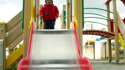 Active Lad Sliding Down The Chute On The Playground Footage