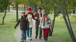 Two kids and their parents walking together in the park Footage