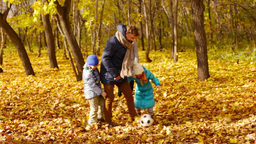 Dad kicking the ball together with his kids in the autumn forest Footage