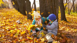 Charming kids playing in the park throwing fallen leaves at each other Footage