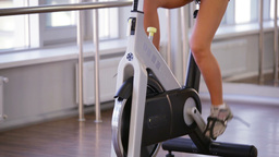 Happy athlete enhancing her endurance while working out on an exercycle Footage
