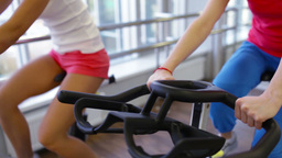 Close-up of healthy women spinning the pedals of exercise bicycles Footage