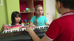Little girl and her friends playing the piano and singing Footage