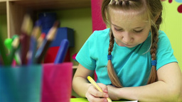 Lovely child being busy drawing with felt-tip pens and pencils Footage