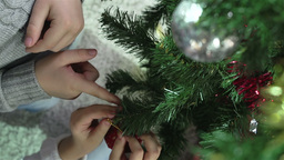 Little boy in Santa hat removing a Christmas bauble from one place to another Footage