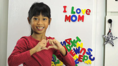 Asian Girl Spelling I Love Mom On Fridge stock footage