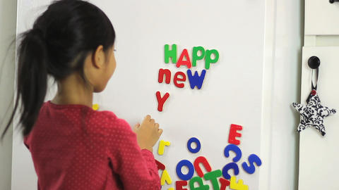 Asian Girl Spelling Happy New Year On Fridge stock footage
