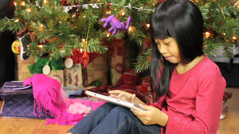 Little Asian Girl Using Tablet Beside Christmas Footage