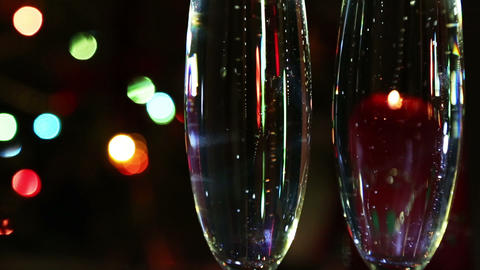 glasses with champagne and candle against festive  Footage