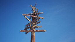Wooden traffic sign pointing to various cities Footage