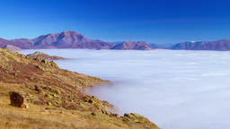 4K timelapsed layer of fog among mountain peaks Footage