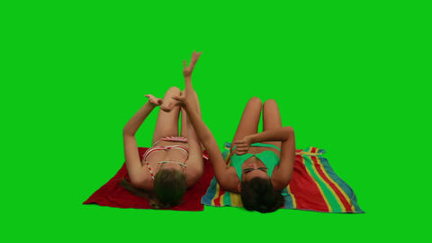Girls lying on the towel and dancing with their ha Footage
