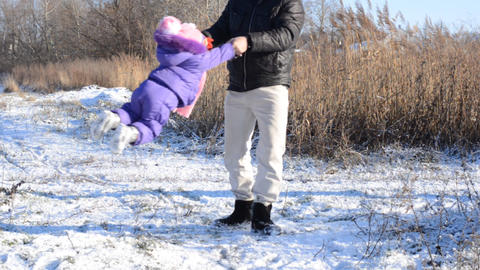 Father Rotates His Little Daughter In Snowy Park stock footage