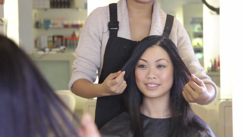 Hairdresser styling hair, talking with customer in mirror Live Action