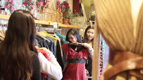 Females looking in clothes shop at clothes in mirror Live Action