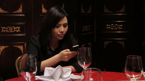 Female in restaurant looking at mobile whilst waiting for date Footage