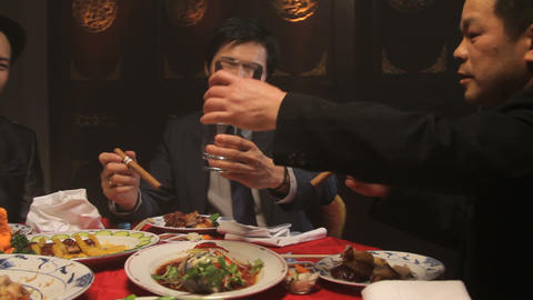 Businessmen toasting drinks and smoking in Chinese restaurant Footage