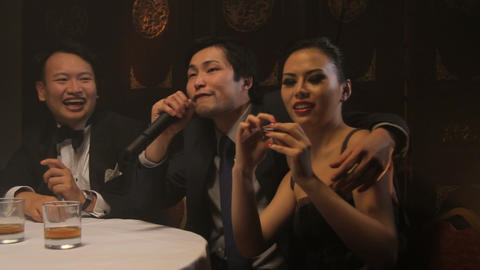 Male singing karaoke in Chinese restaurant, female taking picture Footage