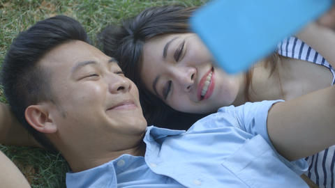 Young couple holding mobile phone with lying on grass Footage