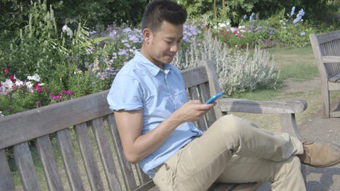 Young man sitting on bench using mobile phone in park Footage