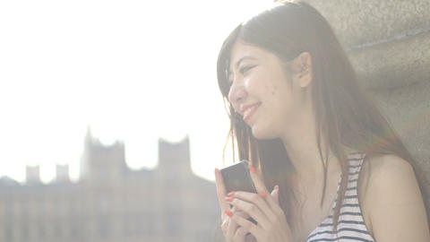 Young woman text messaging with big ben in background Footage