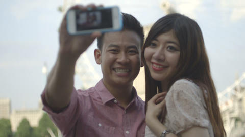 Young couple taking self-portrait with big wheel in background Footage