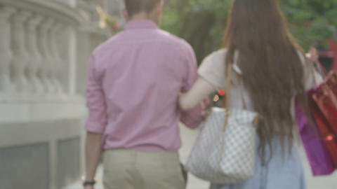 Young couple walking on street with shopping bags Footage
