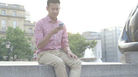 Young man using mobile phone with fountain in back Footage