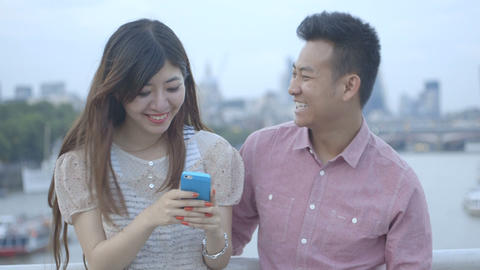 Young couple standing and using mobile phone to outdoor Footage