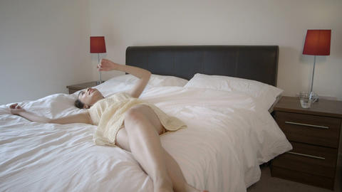Woman jumps onto bed Footage