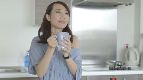 Young woman holding coffee cup and drinking coffee in kitchen Footage