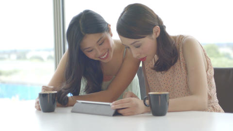 Young women using digital tablet and talking in office Footage