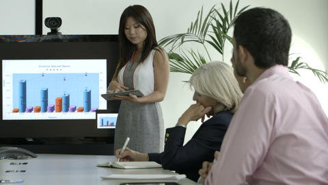 Businesswoman explaining with the help of graph and tablet in board room Footage