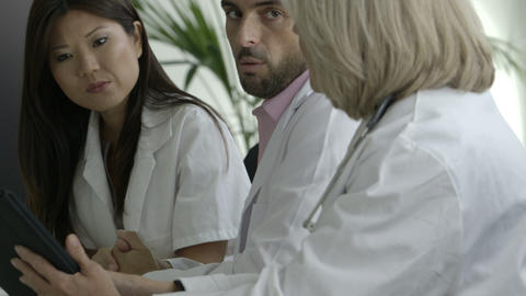 Doctors doing discussion with tablet in meeting room Footage