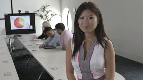 Woman with arms crossed while people working in background Footage